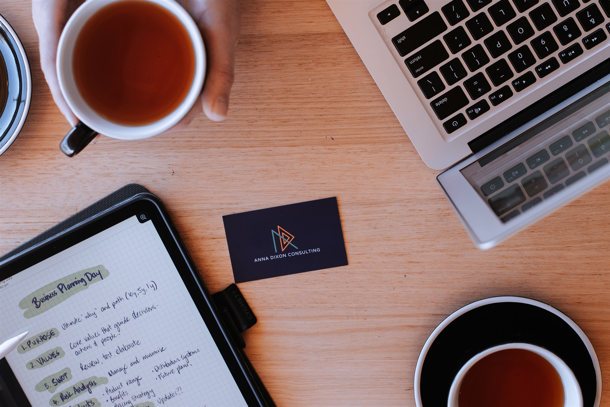 Anna Dixon Consulting business card on a table with an ipad with Business Plan outline displayed, a laptop and two drinks.